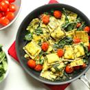 """<p>Looking for a new way to turn a bag of frozen cheese ravioli into a satisfying and healthy dinner? This easy pasta recipe calls for just five ingredients but is loaded with fresh flavors. By using grape tomatoes, prewashed spinach and prepared pesto, we eliminate all prep work, making this 15-minute Caprese-inspired ravioli the ideal weeknight meal. <a href=""""http://www.eatingwell.com/recipe/274007/pesto-ravioli-with-spinach-tomatoes/"""" rel=""""nofollow noopener"""" target=""""_blank"""" data-ylk=""""slk:View recipe"""" class=""""link rapid-noclick-resp""""> View recipe </a></p>"""