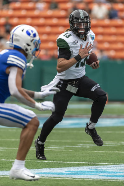 Hawaii quarterback Cole McDonald (13) runs with the football during the first half of the Hawaii Bowl NCAA college football game against BYU, Tuesday, Dec. 24, 2019, in Honolulu. (AP Photo/Eugene Tanner)