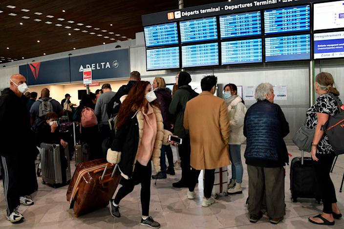 Travellers stands in front of screens displaying departures flights at Paris-Charles-de-Gaulle airport after a US 30-day ban on travel from Europe due to the COVID-19 spread in Roissy-en-France on March 12, 2020. President Trump announced on March 11, 2020 a 30-day ban on travel from mainland Europe over the coronavirus pandemic.