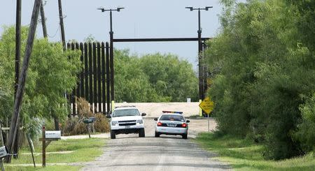 U.S. Border Patrol agents talk in their vehicles at the open gate in the 18-foot (five-metre) high rusty steel barrier along the U.S.- Mexico border near Fernando Rivera Jr.'s home in Brownsville, Texas September 2, 2014. REUTERS/Rick Wilking