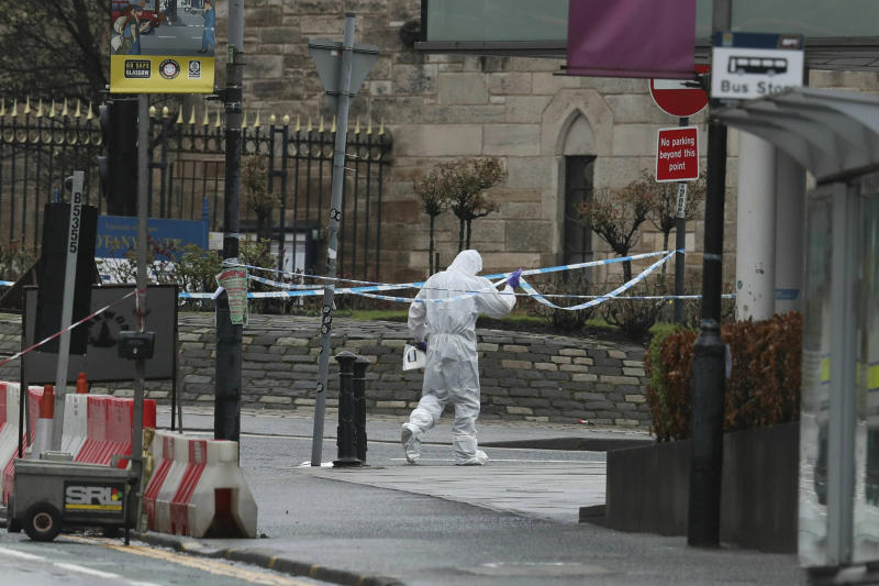 A forensic worker outside the University of Glasgow after the building was evacuated when a suspect package was found in the mailroom, in Glasgow, Scotland, Wednesday March 6, 2019. Buildings at the University of Glasgow were evacuated Wednesday as police examined a suspicious package found in the mailroom, a day after three London transport hubs received letter bombs. (Andrew Milligan/PA via AP)