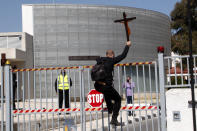 """A protestor holding a cross climbs a gate outside Cyprus' national broadcasting building, during a protest, in capital Nicosia, Cyprus, Saturday, March 6, 2021. The Orthodox Church of Cyprus is calling for the withdrawal of the country's controversial entry into this year's Eurovision song context titled """"El Diablo"""", charging that the song makes an international mockery of country's moral foundations by advocating """"our surrender to the devil and promoting his worship."""" (AP Photo/Petros Karadjias)"""