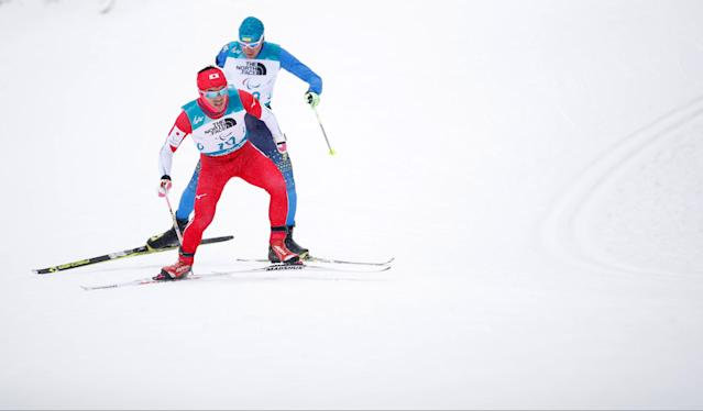 Biathlon - Pyeongchang 2018 Winter Paralympics - Men's 15km - Standing - Alpensia Biathlon Centre - Pyeongchang, South Korea - March 16, 2018 - Keiichi Sato of Japan and Vitalii Sytnyk of Ukraine (rear) compete. REUTERS/Carl Recine