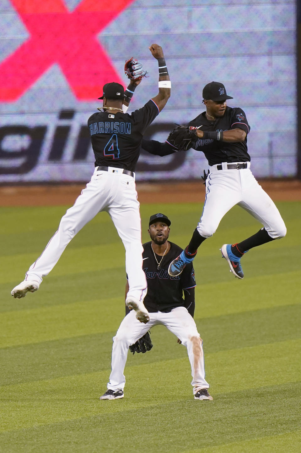 Miami Marlins' Starling Marte, center, watches as Monte Harrison, left, and Lewis Brinson, right, leap in the air as they celebrate the Marlins win over the Philadelphia Phillies in the second game of a baseball doubleheader, Sunday, Sept. 13, 2020, in Miami. (AP Photo/Wilfredo Lee)