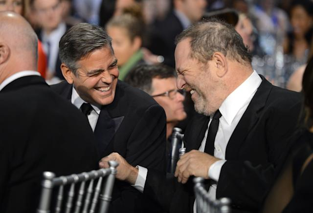"George Clooney and Harvey Weinstein share a laugh in 2013. Clooney called the accusations against Weinstein ""disturbing"" in part because many people may have covered them up."