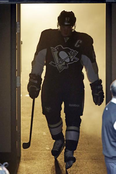 Pittsburgh Penguins' Sidney Crosby heads onto the ice during player introductions before the Penguins' NHL hockey game against the New Jersey Devils in Pittsburgh on Thursday, Oct. 3, 2013. (AP Photo/Gene J. Puskar)