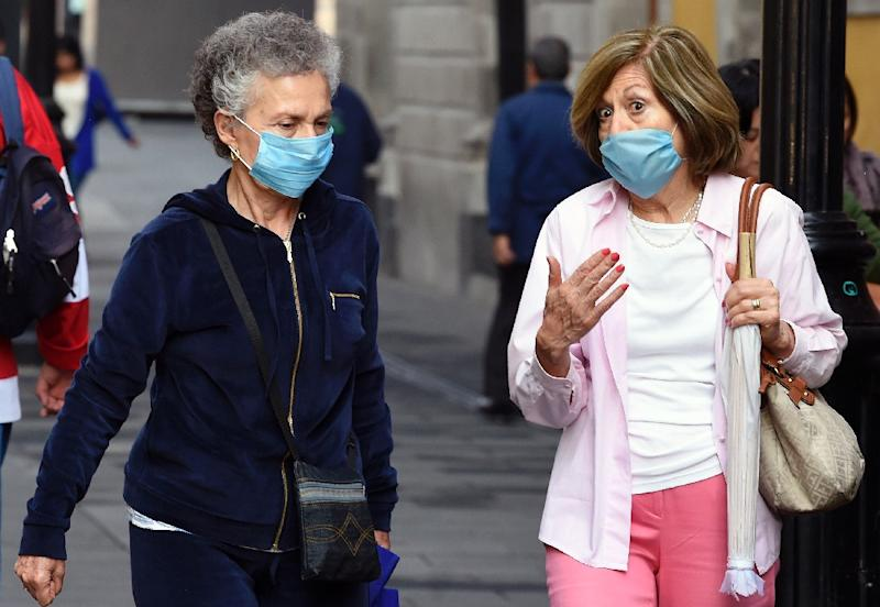 Women wear face masks in Mexico City on May 17, 2019. A thick layer of smog enveloping Mexico City, resulted in an air pollution alert urging people to stay indoors, cancelling school lessons and moving the semi-finals of the first-division football league to another city. (AFP Photo/ALFREDO ESTRELLA)