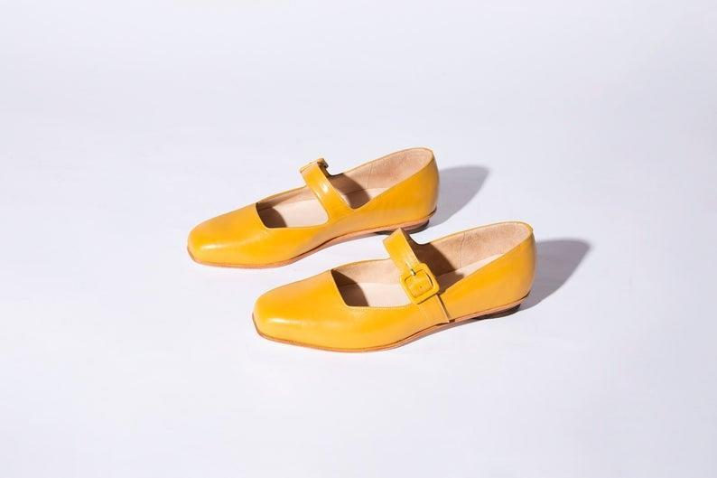 "<h2>Curcuma Eugenia Flat </h2><br>Because we all know a mom, sister, girlfriend, or BFF that prefers shoes over flowers, any day. Gift them a contemporary pair of leather flats. They <a href=""https://www.etsy.com/listing/680552751/eugenia-flat-in-black-glaze"" rel=""nofollow noopener"" target=""_blank"" data-ylk=""slk:also come in black"" class=""link rapid-noclick-resp"">also come in black</a>. <br><br><em>Shop <strong><a href=""https://www.etsy.com/shop/ZOUXOUSHOES"" rel=""nofollow noopener"" target=""_blank"" data-ylk=""slk:ZOUXOUSHOES"" class=""link rapid-noclick-resp"">ZOUXOUSHOES</a></strong></em><br><br><strong>ZOUXOUSHOES</strong> Eugenia Flat in Curcuma, $, available at <a href=""https://go.skimresources.com/?id=30283X879131&url=https%3A%2F%2Fwww.etsy.com%2Flisting%2F895445167%2Feugenia-flat-in-curcuma"" rel=""nofollow noopener"" target=""_blank"" data-ylk=""slk:Etsy"" class=""link rapid-noclick-resp"">Etsy</a>"