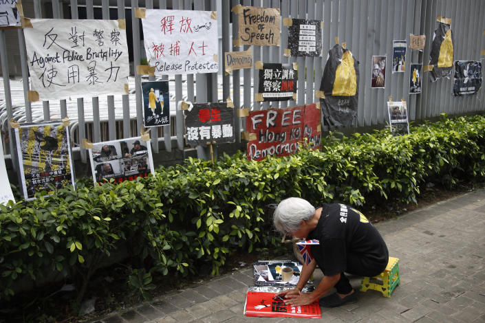 A protester prepares to hang posters against police brutality and calling for the release of arrester protesters outside the Central Government Office building in Hong Kong on Thursday, July 4, 2019. Hong Kong police have announced the arrest of 12 people who tried to disrupt a ceremony Monday marking the anniversary of Hong Kong's return from Britain to China in 1997, and a person was arrested for his alleged involvement in the storming of the legislature building that night.(AP Photo/Andy Wong)