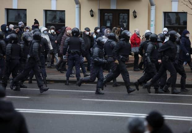 Belarusian law enforcement officers are seen following participants of an opposition rally in Minsk in November 2020.