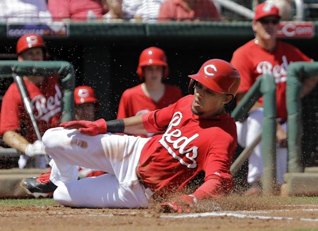 Cincinnati Reds' Billy Hamilton slides home to score from third base on a ground out by Brandon Phillips in the first inning of a spring exhibition baseball game against the Arizona Diamondbacks on Thursday, March 27, 2014, in Goodyear, Ariz. (AP Photo/Mark Duncan)