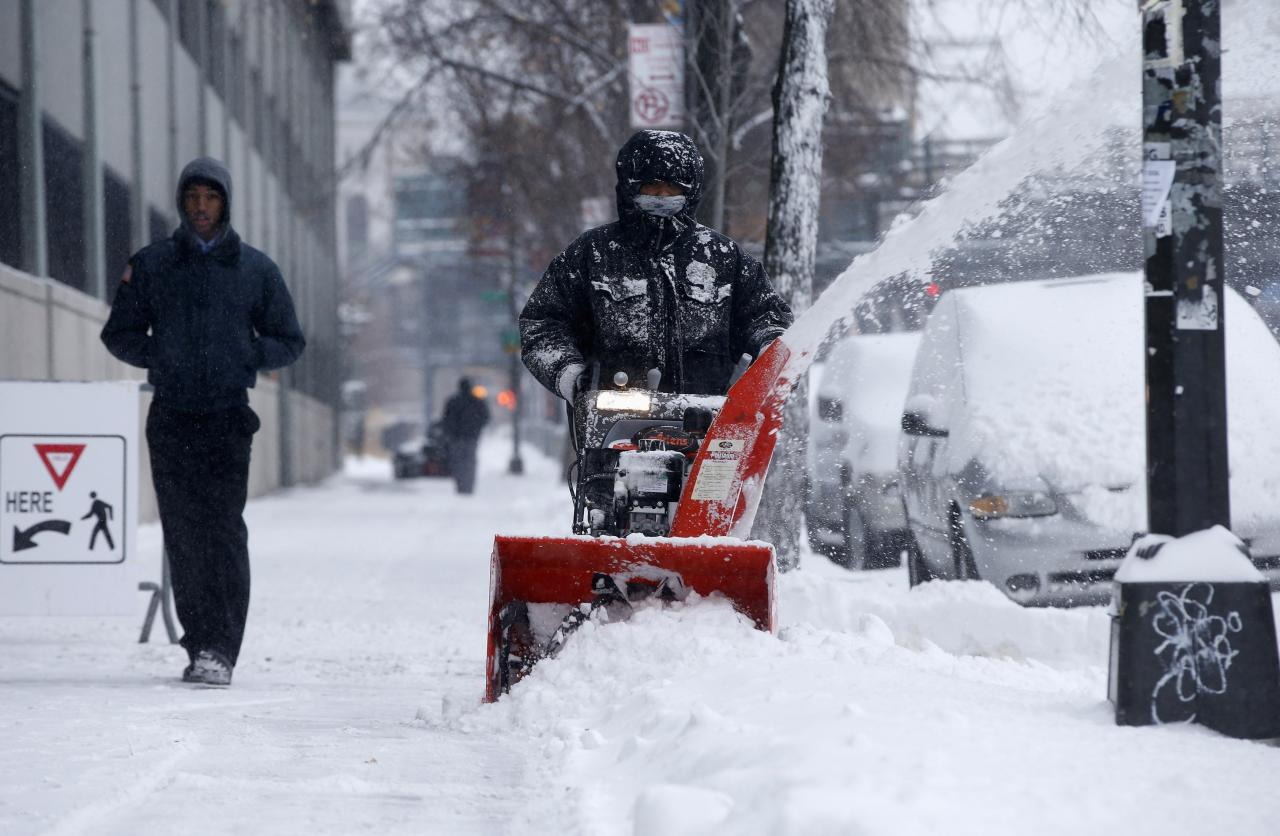 A man clears snow with a snow blower in the South Bronx section of New York City, January 3, 2014. A major snowstorm producing blizzard-like conditions hammered the northeastern United States on Friday, causing more than 1,000 U.S. flight delays and cancellations, paralyzing road travel, and closing schools and government offices. REUTERS/Mike Segar (UNITED STATES - Tags: ENVIRONMENT SOCIETY)