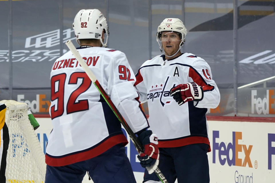 Washington Capitals' Nicklas Backstrom (19) celebrates his goal with Evgeny Kuznetsov during the second period of an NHL hockey game against the Pittsburgh Penguins in Pittsburgh, Sunday, Jan. 17, 2021. (AP Photo/Gene J. Puskar)