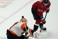 Washington Capitals right wing Daniel Sprong (10) watches the puck roll off the helmet of Philadelphia Flyers goaltender Brian Elliott (37) during the third period of an NHL hockey game, Friday, May 7, 2021, in Washington. The Flyers won 4-2. (AP Photo/Alex Brandon)