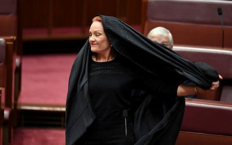 Pauline Hanson pulls off a burqa in the Senate chamber at Parliament House in Canberra - Credit:  REUTERS