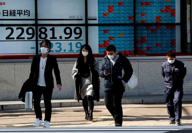 FILE PHOTO: People wearing surgical masks walk past a screen showing Nikkei index outside a brokerage in Tokyo