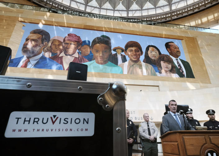 The Transportation Security Administration (TSA) administrator David P. Pekoske, center, talks during a news conference in Los Angeles' Union Station on Tuesday, Aug. 14, 2018. Pekoske talked about the ThruVision suicide vest-detection technology that reveals suspicious objects on people. Aiming to stay ahead of an evolving threat against transit systems worldwide, officials in Los Angeles are testing out the airport-style body scanners that screen subway passengers for firearms and explosives. (AP Photo/Richard Vogel)