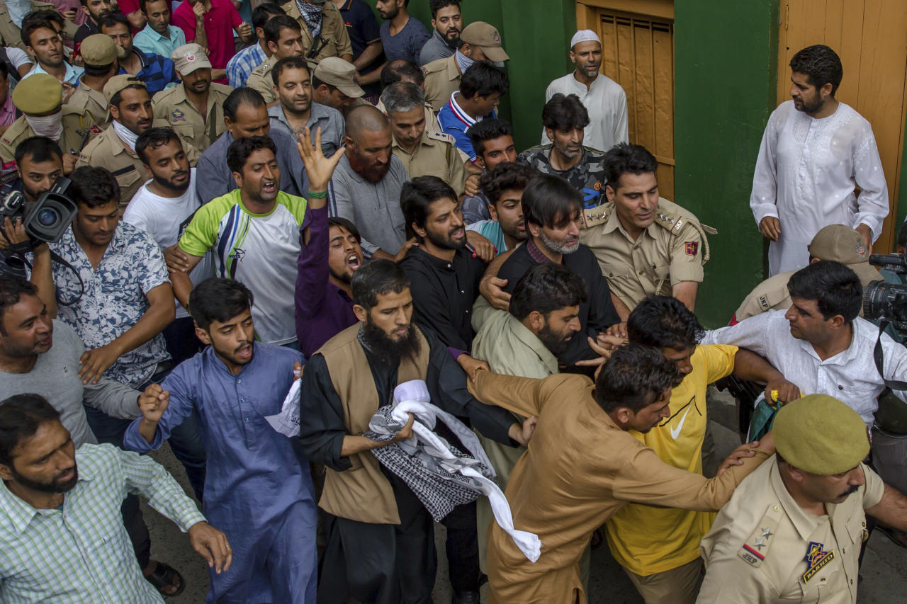 An Indian police officer escorts Jammu Kashmir Liberation Front Chairman Yasin Malik, centre right, after detaining him during a protest march towards United Nations Military Observer Group headquarters in Srinagar, Indian controlled Kashmir, Friday, July 21, 2017. Shops, businesses and schools were closed in most parts of the region because of the general strike, called by separatists who challenge India's sovereignty over Kashmir. (AP Photo/Dar Yasin)