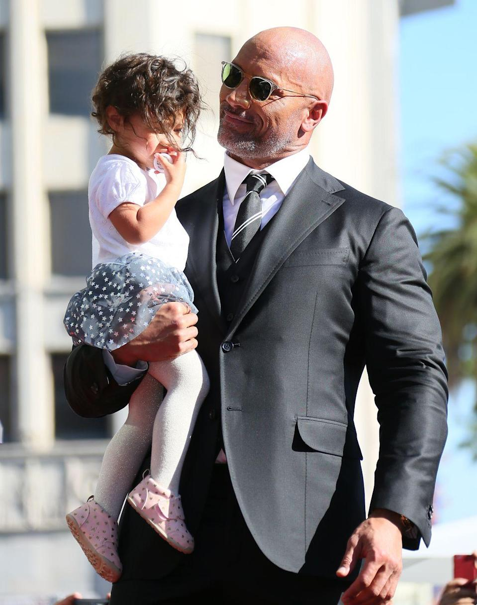 """<p><strong>Children</strong>: Simone Alexandra Johnson (18), Jasmine Johnson (4), Tiana Gia Johnson (2)</p><p><a href=""""https://people.com/celebrity/sexiest-man-alive-2016-dwayne-johnson-the-rock/"""" rel=""""nofollow noopener"""" target=""""_blank"""" data-ylk=""""slk:People's 2016 Sexiest Man Alive"""" class=""""link rapid-noclick-resp"""">People's 2016 Sexiest Man Alive</a> may look tough and muscular on the outside, but the dad of three has a <a href=""""https://www.oprahmag.com/entertainment/a23865997/dwayne-johnson-daughter-singing-instagram/"""" rel=""""nofollow noopener"""" target=""""_blank"""" data-ylk=""""slk:soft spot for his daughters"""" class=""""link rapid-noclick-resp"""">soft spot for his daughters</a>, <a href=""""https://www.oprahmag.com/entertainment/a30663865/dwayne-the-rock-johnson-oprah-2020-vision-tour-father-death/"""" rel=""""nofollow noopener"""" target=""""_blank"""" data-ylk=""""slk:telling Oprah that family is his &quot;anchor.&quot;"""" class=""""link rapid-noclick-resp"""">telling Oprah that family is his """"anchor.""""</a> He is raising his younger two children with <a href=""""https://www.oprahmag.com/entertainment/a28355589/the-rock-wife-lauren-hashian/"""" rel=""""nofollow noopener"""" target=""""_blank"""" data-ylk=""""slk:wife Lauren Hashian"""" class=""""link rapid-noclick-resp"""">wife Lauren Hashian</a> while his eldest (who he co-parents with <a href=""""https://www.oprahmag.com/entertainment/a29386404/dwayne-the-rock-johnson-instagram-ex-dany-garcia-bodybuilder/"""" rel=""""nofollow noopener"""" target=""""_blank"""" data-ylk=""""slk:ex-wife Dany Garcia"""" class=""""link rapid-noclick-resp"""">ex-wife Dany Garcia</a>) is following in his footsteps, by <a href=""""https://www.wwe.com/shows/wwenxt/article/simone-johnson-wwe-performance-center"""" rel=""""nofollow noopener"""" target=""""_blank"""" data-ylk=""""slk:training to become a WWE wrestler"""" class=""""link rapid-noclick-resp"""">training to become a WWE wrestler</a>.</p>"""
