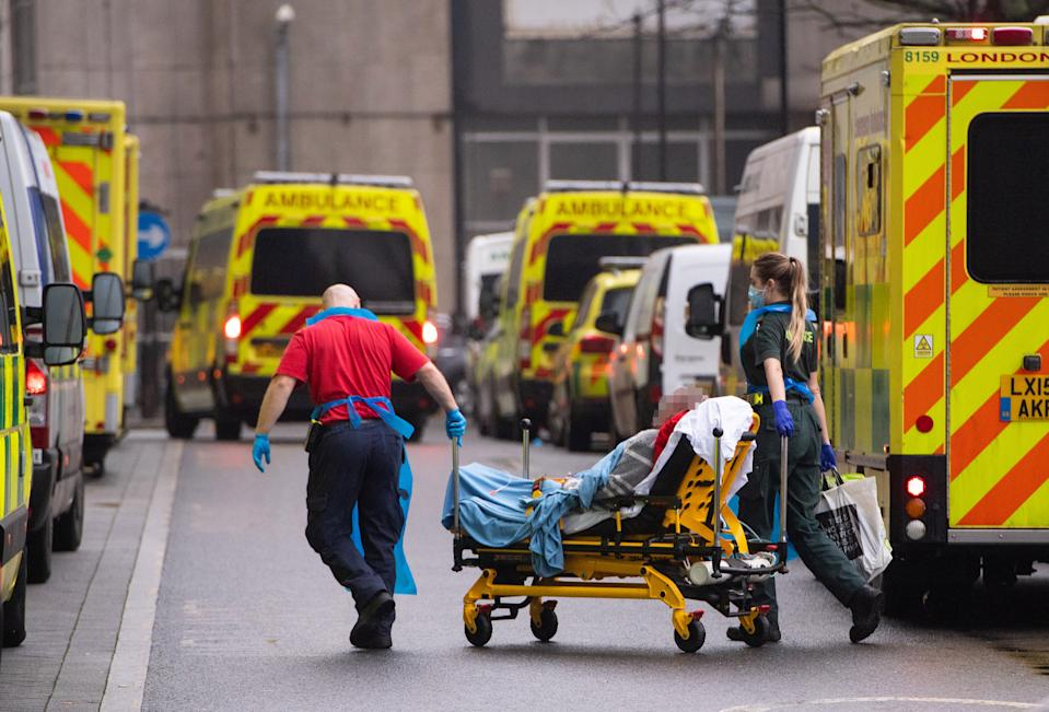 IMAGE PIXELLATED BY PA PICTURE DESK Paramedics unload a patient from an ambulance outside the Royal London Hospital in London. (Photo by Dominic Lipinski/PA Images via Getty Images)