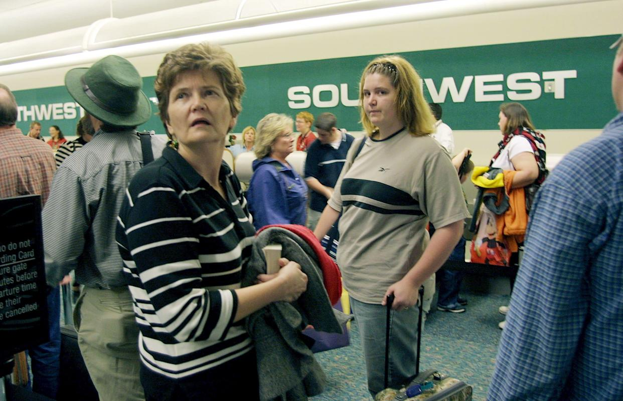 Passengers wait in line at the low-cost carrier Southwest Airlines ticket counter at Orlando International Airport in Orlando, Florida on Dec. 13, 2002.