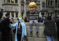 FILE - In this Tuesday, Sept. 24, 2019 file photo a person dressed as a caricature of British Prime Minister Boris Johnson in a prison uniform stands outside the Supreme Court in London after it made it's decision on the legality of Johnson's five-week suspension of Parliament. Britain and the European Union have struck a provisional free-trade agreement that should avert New Year's chaos for cross-border commerce and bring a measure of certainty to businesses after years of Brexit turmoil. The breakthrough on Thursday, Dec. 24, 2020 came after months of tense and often testy negotiations that whittled differences down to three key issues: fair-competition rules, mechanisms for resolving future disputes and fishing rights. (AP Photo/Matt Dunham, file)