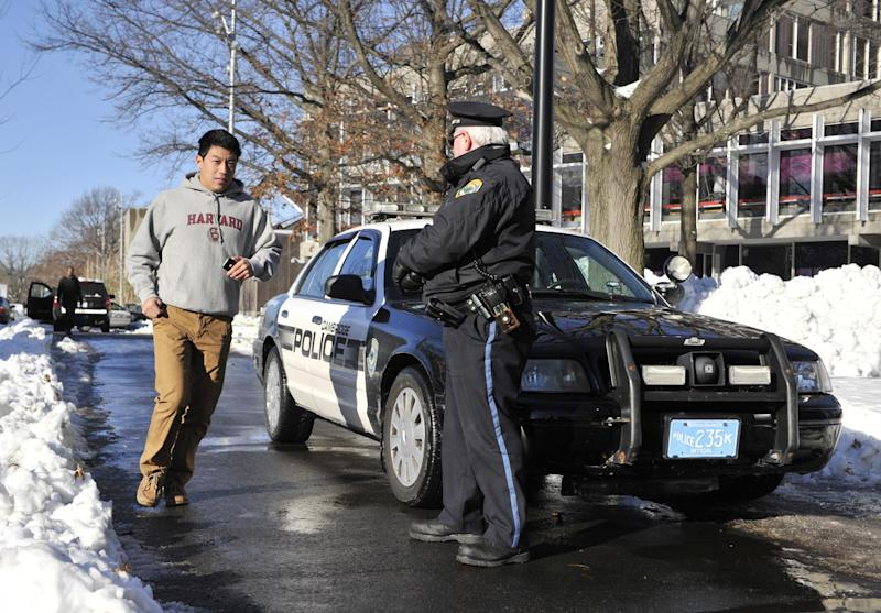 A police officer secures an area at Harvard University in Cambridge, Mass., Monday, Dec. 16, 2013. Four buildings on campus were evacuated after campus police received an unconfirmed report that explosives may have been placed inside, interrupting final exams. (AP Photo/Josh Reynolds)