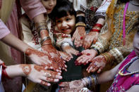 Muslim girls display their hands painted with traditional henna to celebrate Eid al-Fitr holidays, marking on the end of the fasting month of Ramadan, in Peshawar, Pakistan, Thursday, May 13, 2021. (AP Photo/Muhammad Sajjad)