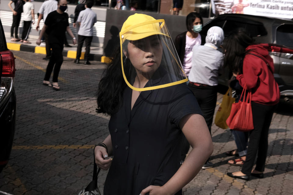 A woman wears a face shield as a precaution against the new coronavirus outbreak serve customers at a McDonald's restaurant in Jakarta, Indonesia, Sunday, May 10, 2020. (AP Photo/Dita Alangkara)