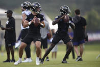 Baltimore Ravens quarterbacks Trace McSorley, left, and Tyler Huntley throw during an NFL football training camp practice, Thursday, July 29, 2021, in Owings Mills, Md.(AP Photo/Gail Burton)