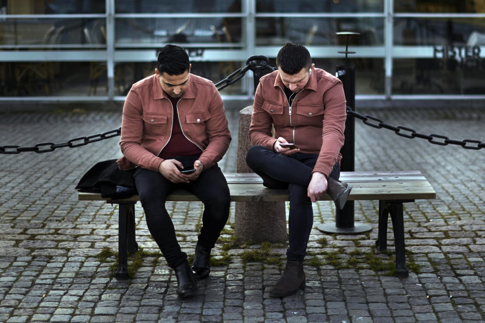 FILE - In this Wednesday, April 8, 2020 file photo two men check their phones as they sit near the harbor in Stockholm, Sweden. (AP Photo/Andres Kudacki, File)