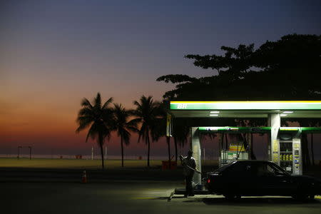 A worker prepares to fill a car at a gas station close to Copacabana beach in Rio de Janeiro, January 12, 2015. REUTERS/Ricardo Moraes