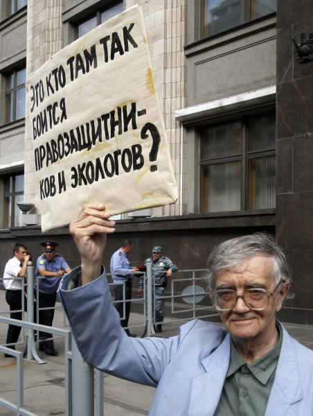 A protester holds a slogan reading: 'Who is afraid of human rights activists and ecologists there (in the government)?' outside the parliament headquarters in Moscow, Russia, Friday, July 6, 2012. The Russian lower parliament house is expected to give preliminary approval to the bill on Friday, that would impose harsh regulations on all foreign-funded non-governmental organizations that are involved in political activity, part of a broad crackdown on civil activism and dissent that has accompanied Vladimir Putin's return to the presidency in May.(AP Photo/Misha Japaridze)