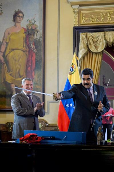 Rosneft's CEO Igor Sechin presented Venezuelan President Nicolas Maduro with a sword during the signing of agreements at Miraflores presidential Palace in Caracas last year. (AFP Photo/FEDERICO PARRA)