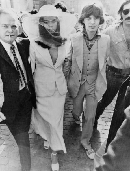 <p>Mick Jagger and Bianca Jagger attempted to keep their St. Tropez nuptials a secret, but once word spread that they were en route to the courthouse, photographers flocked to them. Bianca's outfit, a white Yves Saint Laurent suit and veiled wide-brimmed hat, is iconic today.</p>