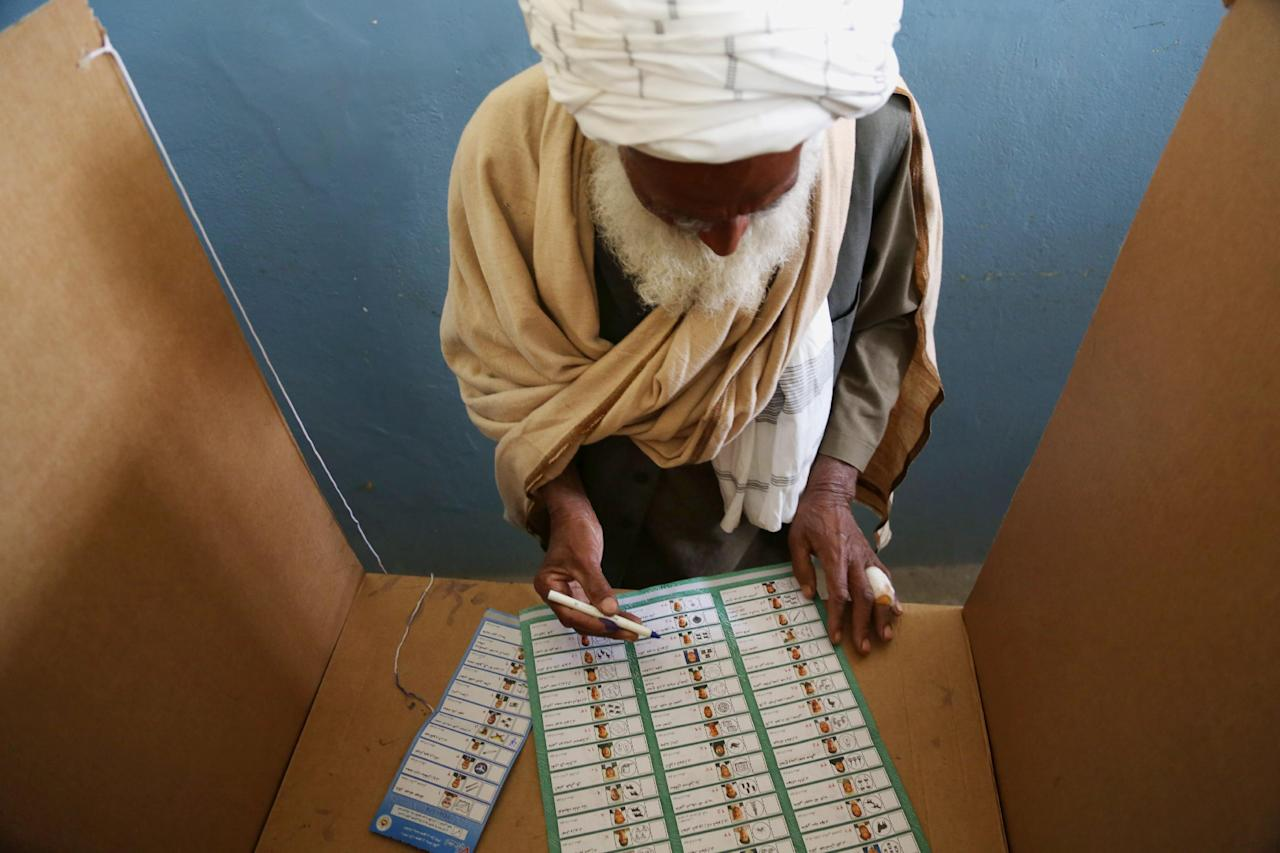 An Afghan man fills his ballot at a polling station in Jalalabad, east of Kabul, Afghanistan, Saturday, April 5, 2014. Afghan voters lined up for blocks at polling stations nationwide on Saturday, defying a threat of violence by the Taliban to cast ballots in what promises to be the nation's first democratic transfer of power. The vote will decide who will replace President Hamid Karzai, who is barred constitutionally from seeking a third term. (AP Photo/Rahmat Gul)