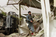 A security officials inspects the site of a car bomb attack in Herat province, west of Kabul, Afghanistan, Saturday, March 13, 2021. A powerful car bomb killed numerous people and injured dozens more in Afghanistan's western Herat province, officials said Saturday. (AP Photo/Hamed Sarfarazi)