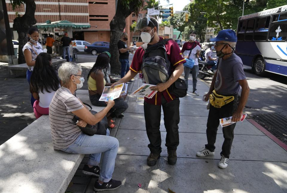 """Juan Pablo Lares distributes free copies of a newspaper """"Enterate"""" to people at a bus stop in Caracas, Venezuela, Saturday, July 31, 2021. Two decades of governments that see the press as an enemy have pushed Venezuelan journalists to find alternative ways to keep citizens informed. (AP Photo/Ariana Cubillos)"""