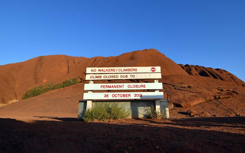 New signage marking a permanent ban on climbing Uluru, also known as Ayers Rock, is seen at the base of the monolith at Uluru-Kata Tjuta National Park in Australia's Northern Territory on October 25, 2019. | SAEED KHAN/Getty Images