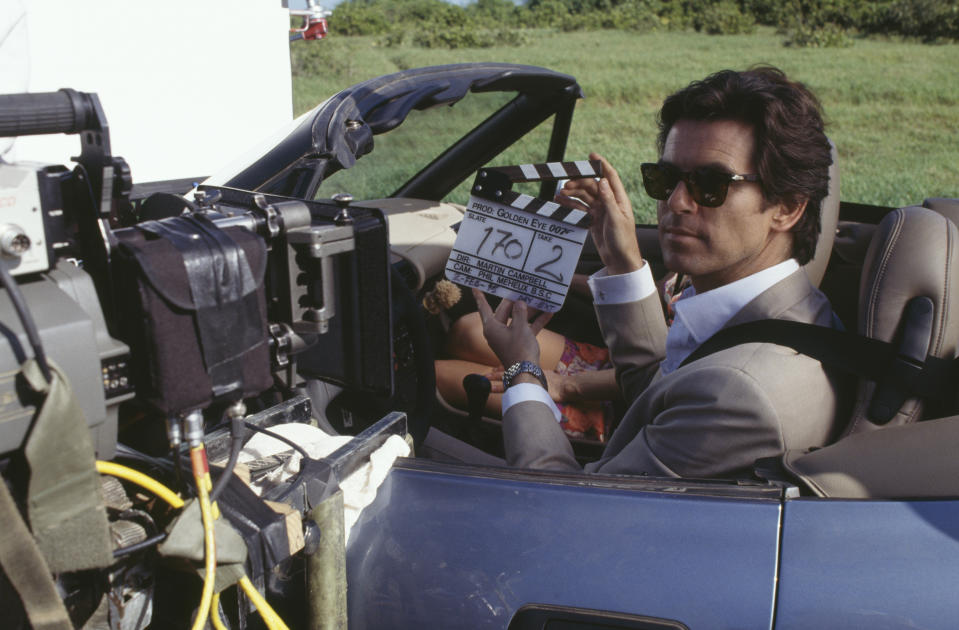 Irish actor Pierce Brosnan as 007, driving a BMW Z3 for a scene in the James Bond film 'GoldenEye', 2nd February 1995. Polish actress Izabella Scorupco is in the seat behind him. Here Brosnan operates the clapperboard for the camera. (Photo by Keith Hamshere/Getty Images)