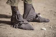 In this Tuesday, Aug. 2, 2016 photo, a frankinsence tapper wears cloth wrapped on his feet to keep sticky resin from his skin and shoes near Gudmo, Somaliland, a breakaway region of Somalia. These last intact wild frankincense forests on Earth are under threat as prices have shot up in recent years with the global appetite for essential oils, and overharvesting has led to the trees dying off faster than they can replenish, putting the ancient resin trade at risk. (AP Photo/Jason Patinkin)