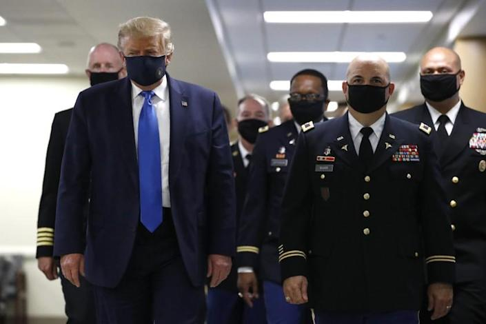 """President Trump wore a mask Saturday during a visit to Walter Reed National Military Medical Center in Bethesda, Md. <span class=""""copyright"""">(Patrick Semansky / Associated Press)</span>"""