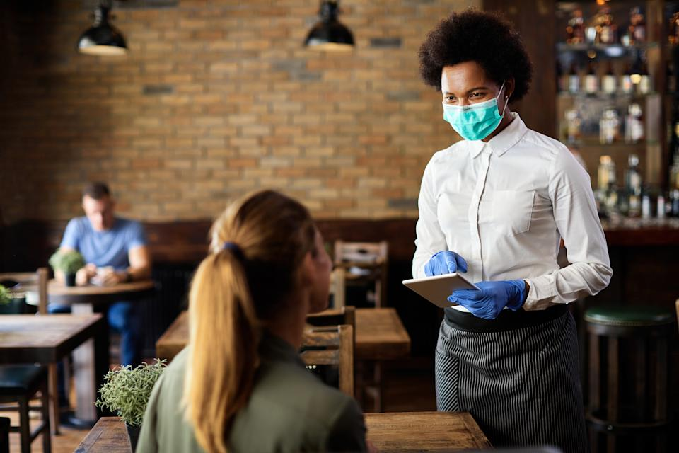 Happy black waitress wearing protective face mask while taking order from customer on a touchpad in a cafe.