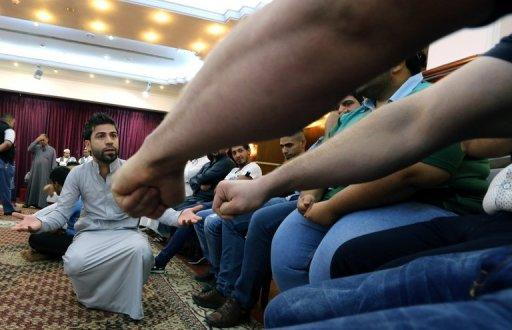 "An Iraqi man takes part in a game of ""Mheibis"" -- where someone has to guess who is holding a ring in the clenched fist -- in Baghdad, on August 6, 2013. The game of ""Mheibis"" is wildly popular in Iraq during the holy Muslim fasting month of Ramadan"