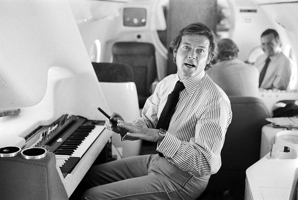 <p>Roger Moore plays an electric keyboard onboard a private jet in 1975. </p>