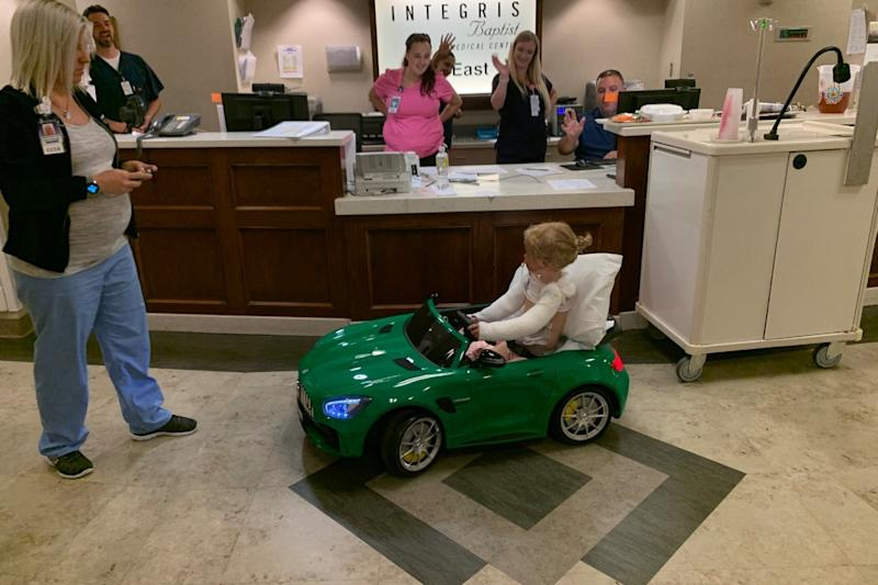 Paetyn pictured driving around the hospital in a toy car. (GoFundMe)