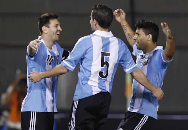 ALTERNATIVE CROP OF ASU109.- Argentina's Lionel Messi, center, celebrates after scoring with teamamtes, Fernando Gago, and Sergio Aguero, right, against Paraguay during a World Cup qualifying soccer game in Asuncion, Paraguay, Tuesday, Sept. 10, 2013. (AP Photo/Jorge Saenz)