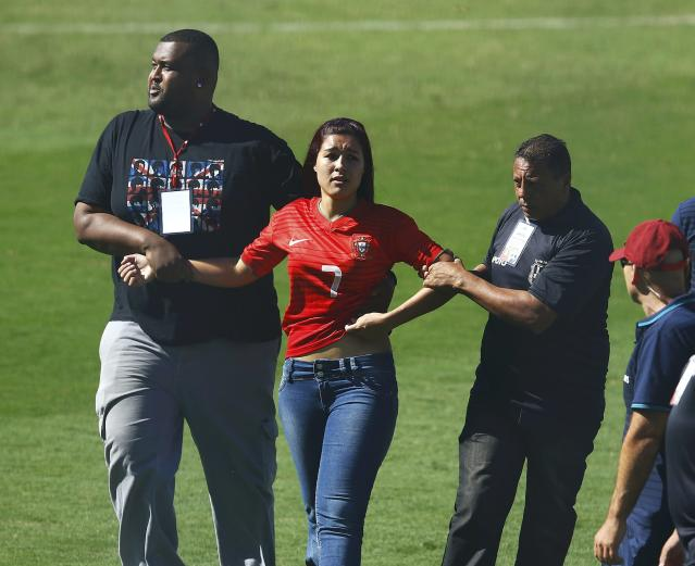 Security guards stop a fan from running towards Portugal's Cristiano Ronaldo during the team training session in Campinas, June 12, 2014. Portugal is preparing for their first soccer match of the 2014 World Cup against Germany on June 16. REUTERS/Mauro Horital (BRAZIL - Tags: SPORT SOCCER WORLD CUP)