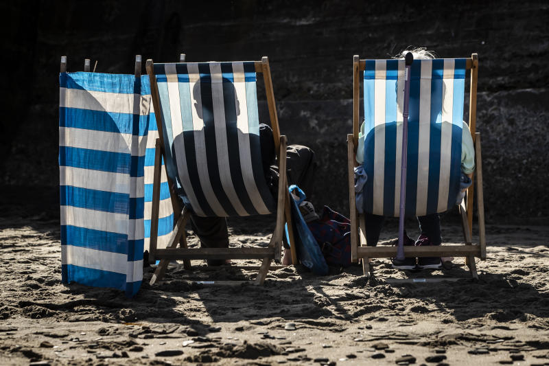People cast shadows on to their deckchairs as they sunbath on Whitby beach in Yorkshire, as temperatures are expected to soar to 26C in some parts of the country this weekend. (Photo by Danny Lawson/PA Images via Getty Images)