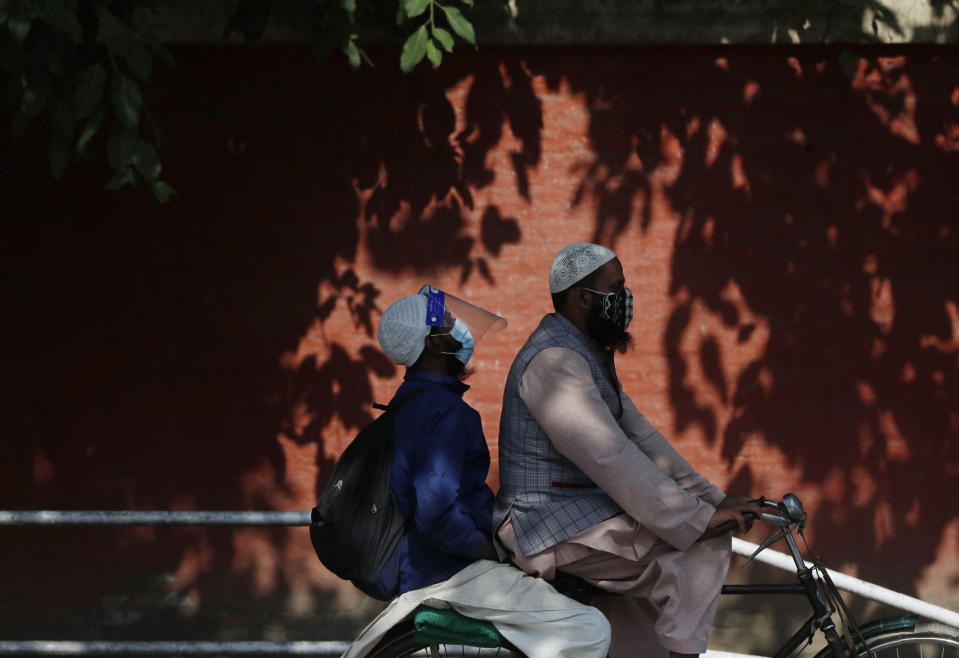 Nepalese men wearing face masks ride on a bicycle in Kathmandu, Nepal, Wednesday, May 5, 2021. Authorities extended lockdown in the capital Kathmandu and surrounding districts by another week on Wednesday as the Himalayan nation recorded the highest COVID-19 daily infection and death. (AP Photo/Niranjan Shrestha)